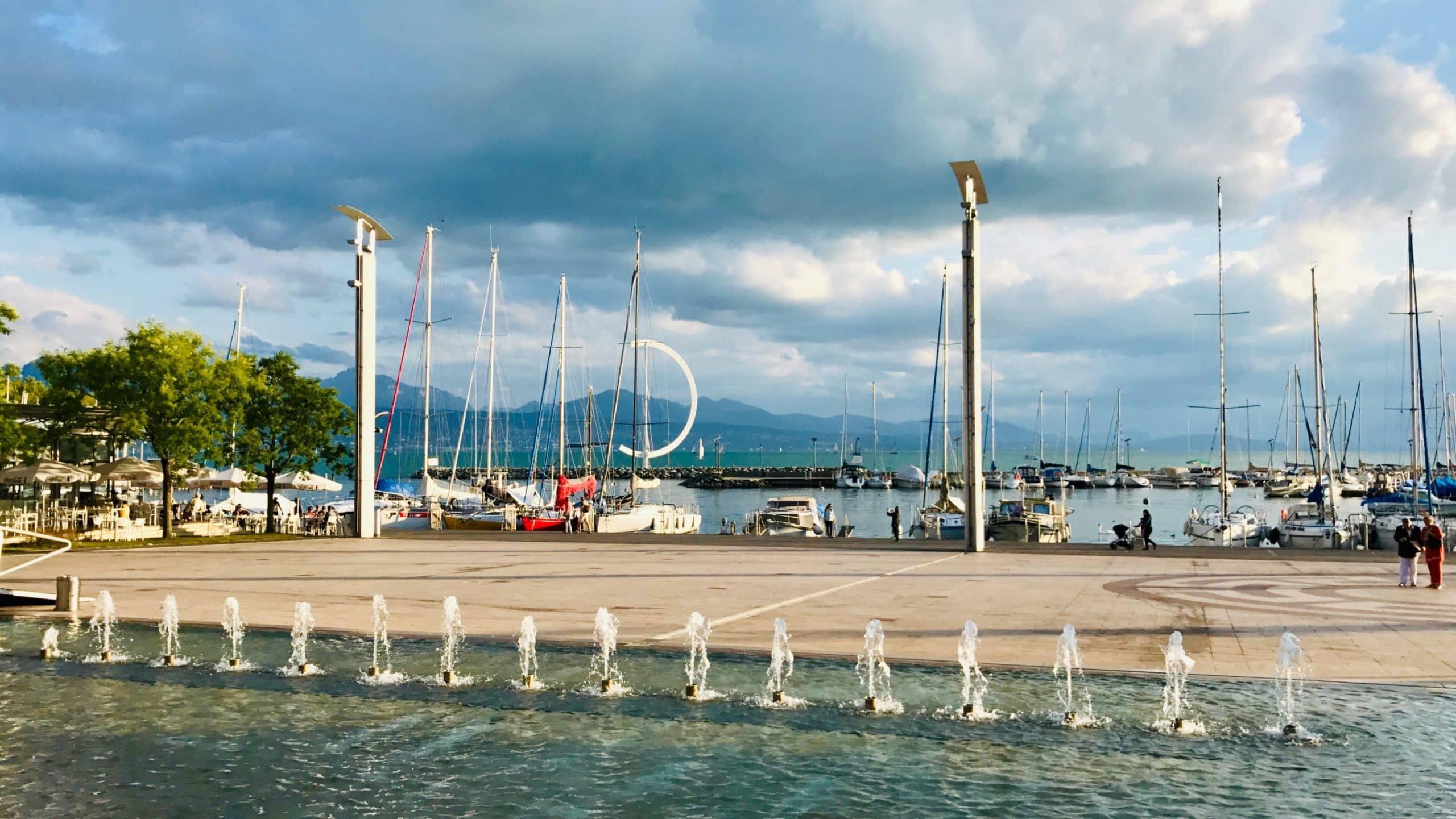 Place de la Navigation. Jets d'eau au premier plan, esplanade au second et le lac avec en arrière-fond les montagnes françaises.